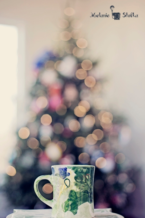 Enjoying a cup of coffee in front of the Christmas tree.