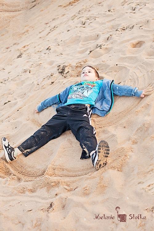 Itty Bitty making sand angels.